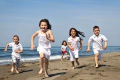 Glückliche Kindgruppe, die auf Strand spielt Lizenzfreie Stockfotos