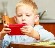 Glückliche Kindheit. Blondes Jungenkinderkind, das mit Handy spielt Lizenzfreie Stockfotografie