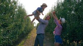 Glückliche Kindheit in der ländlichen Familie, starker Vater wirft Sohn zu wellenartig bewegenden Händen des Himmels und der Mutt stock video footage