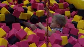 Glückliche Kindheit eines modernen Kindes in der Stadt - der Junge, der Spaß in einem Vergnügungspark hat stock video footage