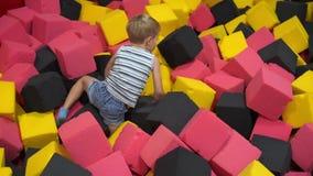 Glückliche Kindheit eines modernen Kindes in der Stadt - der Junge, der Spaß in einem Vergnügungspark hat stock footage