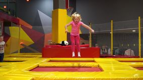 Glückliche Kindheit eines modernen Kindes in der Stadt - Mädchen, das in den Trampolinepark springt stock footage