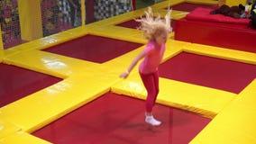 Glückliche Kindheit eines modernen Kindes in der Stadt - Mädchen, das in den Trampolinepark springt stock video footage