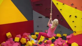 Glückliche Kindheit eines modernen Kindes in der Stadt - Mädchen in einem Vergnügungspark, der ein Seil reitet stock footage