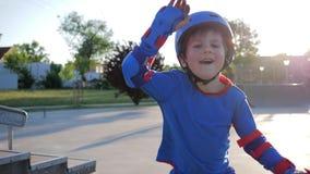 Glückliche Kindheit, frohes Kind im Sturzhelm wendet aktiv Freizeit am Rochen-Park auf Freilicht im Sonnenlicht auf