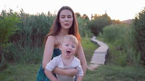 Glückliche Kindheit, junge nette Mama spielt mit süßem Baby, das in einer Luft an den Mutterhänden fliegt stock video