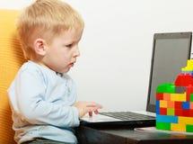 Glückliche Kindheit. Jungenkinderkind, das auf Laptop spielt. Zu Hause. Stockfotos