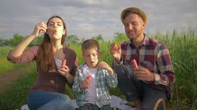 Glückliche Kindheit, lustiger Vater mit Schlagblasen der Mutter und des Jungen und dem Lächeln während der Feiertage auf Freilich stock video footage