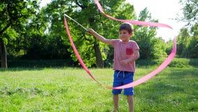 Glückliche Kindheit, nettes Kind wird mit rosa Band auf grüner Lichtung gespielt stock footage