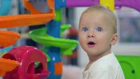 Glückliche Kindheit, reizendes Baby spielte im Kinderraum auf unfocused Hintergrund stock video
