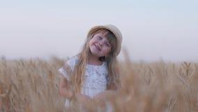 Glückliche Kindheit, wenig schönes angemessenes behaartes Kindermädchen lächelt und dreht ihre Hauptstellung in den goldenen Korn stock video footage