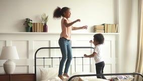 Glückliche kleine afrikanische Kinder Junge und Mädchen, die auf Bett springen
