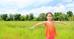 Glückliche kleine asiatische Kindermädchen-Ausdehnungsarme und entspannt an den jungen grünen Reisfeldern stockfotografie