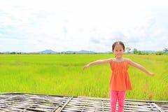 Glückliche kleine asiatische Kindermädchen-Ausdehnungsarme und entspannt an den jungen grünen Reisfeldern mit Gebirgs- und Wolken lizenzfreie stockbilder