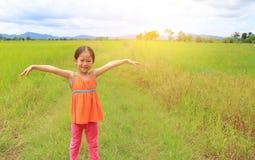 Glückliche kleine asiatische Kindermädchen-Ausdehnungsarme und entspannt an den jungen grünen Reisfeldern mit Gebirgs- und Wolken stockfotografie