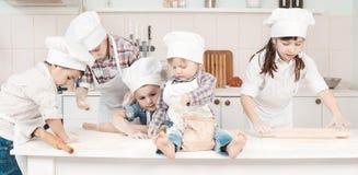Glückliche kleine Chefs, die Teig in der Küche zubereiten Stockfotografie