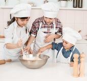 Glückliche kleine Chefs, die Teig in der Küche zubereiten Stockbilder