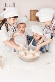 Glückliche kleine Chefs, die Teig in der Küche zubereiten Lizenzfreies Stockbild