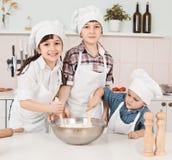 Glückliche kleine Chefs, die Teig in der Küche zubereiten Lizenzfreie Stockbilder