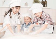 Glückliche kleine Chefs, die Teig in der Küche zubereiten Lizenzfreies Stockfoto
