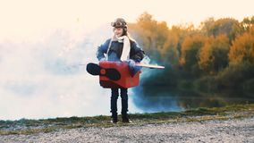 Glückliche kleine Fliegermädchenstellung nahe See im Pappflachen Kostüm mit dem blauen Farbrauche, der Versuchszeitlupe spielt stock video footage