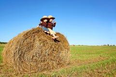 Glückliche kleine Jungen auf dem Bauernhof, der auf Hay Bale sitzt Stockbild