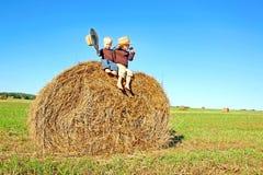 Glückliche kleine Jungen, die auf großem Hay Bale auf dem Bauernhof-Gebiet sitzen Stockfoto