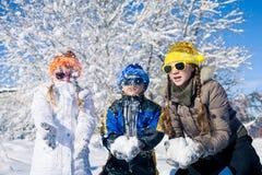 Glückliche kleine Kinder, die am Winterschneetag spielen Stockbild