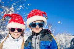 Glückliche kleine Kinder, die am Winterschneetag spielen Stockfoto