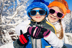 Glückliche kleine Kinder, die am Winterschneetag spielen Stockfotos