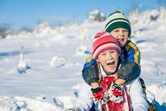 Glückliche kleine Kinder, die am Winterschneetag spielen Stockbilder