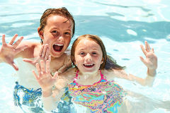 Glückliche kleine Kinder, die zusammen im Pool schwimmen Lizenzfreies Stockbild