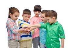 Glückliche kleine Kinder mit den Händen auf die Oberseite Lizenzfreie Stockbilder