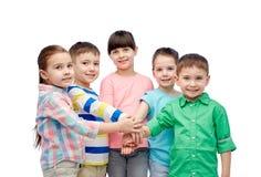 Glückliche kleine Kinder mit den Händen auf die Oberseite Lizenzfreies Stockfoto