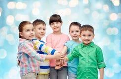 Glückliche kleine Kinder mit den Händen auf die Oberseite Lizenzfreies Stockbild