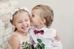 Glückliche kleine Kinderumarmung und -kuß Stockbilder