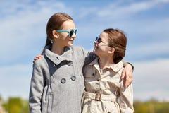 Glückliche kleine Mädchen, die draußen umarmen und sprechen lizenzfreie stockbilder