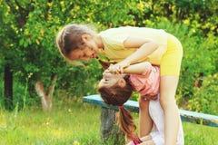 Glückliche kleine Mädchen, die Spaß am Sommertag im Garten haben Stockfotos