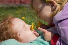 Glückliche kleine Mädchen mit Löwenzahn Stockfotos