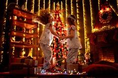 Glückliche kleine Mädchen, welche die Weihnachtspyjamas spielen durch einen Kamin in einem gemütlichen dunklen Wohnzimmer auf Wei lizenzfreies stockbild