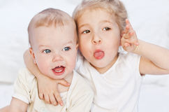 Glückliche kleine Schwester, die ihren Bruder umarmt Stockbild