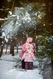 Glückliche kleine Schwestern haben Spaß im schneebedeckten Wald lizenzfreie stockbilder
