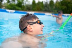 Glückliche Kleinkinder im Poolschießen mit Wasserwerfer lizenzfreies stockbild