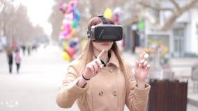 Glückliche Kopfhörergläser vr der virtuellen Realität der jungen Frau tragende in der Beige outwear den Mantel, der Spaß draußen  stock video footage