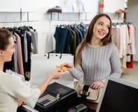 Glückliche Kundin, die mit Kreditkarte zahlt Stockbild