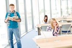 Glückliche Kursteilnehmer mit Buch und Laptop im Klassenzimmer Lizenzfreie Stockfotografie