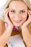 Glückliche Kursteilnehmerfrau schreiben Heimarbeit am Tisch Stockfoto