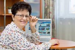 Glückliche lächelnde ältere Frau, die am Notizbuch sitzt und Bilder auf Reise-Websites schaut Stockfotografie