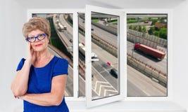 Glückliche lächelnde ältere Frau steht innere nahe dreifache PVC-Fensterscheibe mit hoisy Landstraße mit Autos auf Hintergrund Stockfotografie