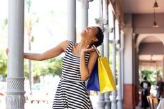Glückliche lächelnde afrikanische Frau streifte das Kleid, das Einkaufstasche hält stockfoto